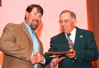 Man on stage receiving award