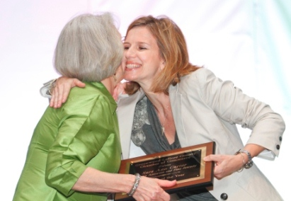 Woman on stage receiving award